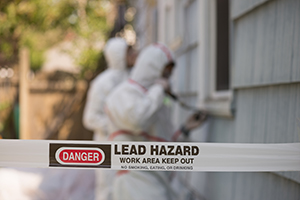 Workers in full body suits removing lead paint with tape in the foreground that says LEAD HAZARD Work Area Keep Out